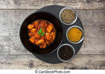 Chicken tikka masala in bowl on wooden table