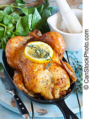 Whole roasted chicken on a pan. Rustic style.