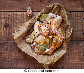 Chicken wings and knives in spices with garlic and bay leaf on a craft bag are on the table