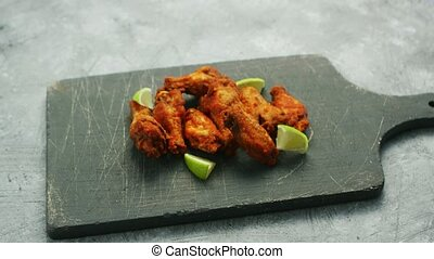 Chicken wings with lime slices - Shabby wooden board with...