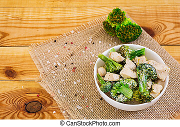 Chicken with broccoli on a wooden background