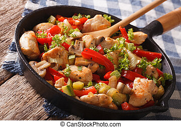 chicken with mushrooms and vegetables on a pan close-up. horizontal