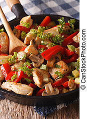 chicken with mushrooms and vegetables on a pan close-up. Vertical