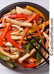 chicken with vegetables close-up on a plate. top view vertical