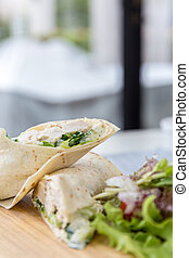Chicken wrap with fresh vegetable on table.