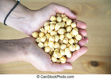 Chickpeas in woman's hands, top view