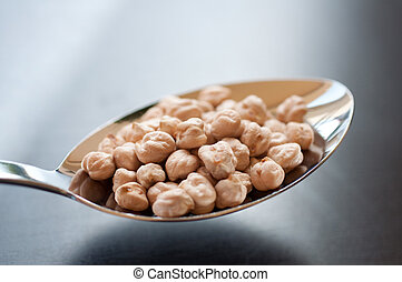 Dried chickpeas on a stainless steel spoon
