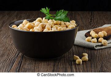 Chickpeas on ceramic bowl on dark wooden background.