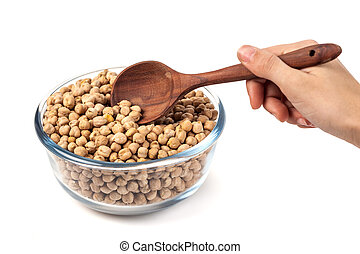 Chickpeas on glass bowl with wooden spoon in hand on white background