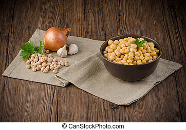 Chickpeas on ceramic bowl on dark wooden background.