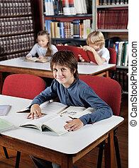 chico que sienta, en la mesa, con, libros, con, compañeros de clase, en, plano de fondo