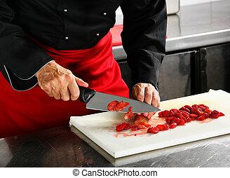 Chief cuts strawberry - Chief in black cuts strawberry on...