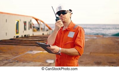 chief officer on deck of ship or vessel with checklist -...