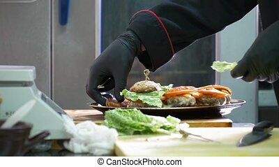 Chief on commercial kitchen serves burgers on the plate - ...