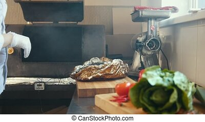 Chief on kitchen of restaurant is preparing of a large piece of smoked meat on a wooden board