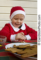 Child (3 years old) decorating gingerbread cookies with icing and chocolates.