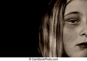 A young girl looking sullen because of child abuse and depression, isolated against a black background