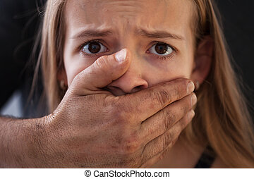 Child abuse concept - male hand covering a frightened young girl mouth