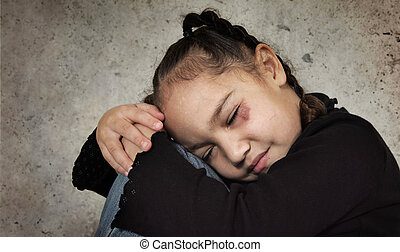 Child abuse - young girl sits next to a concrete wall. She...