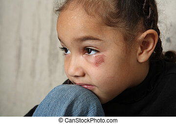 Child abuse - young girl sits next to a concrete wall. She ...