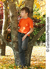 Child among colourful autumn trees and leaves