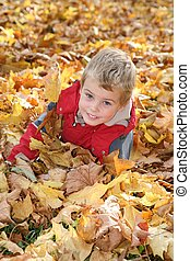child among fallen leaves