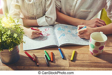 painting a coloring book - Child and adult are painting a ...