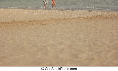 Child and adult running, seashore. Legs of people in...