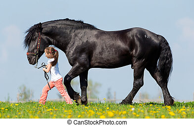 Child and big black horse at spring