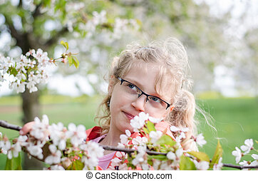 child and blossoming flowers in garden