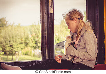child and cat alone by the window
