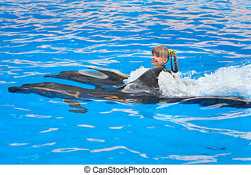 Child and dolphins swimming in blue water.