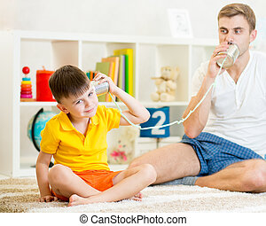 Child and father having a phone call with tin cans