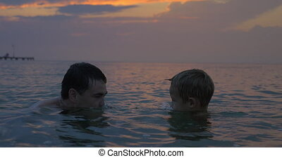 Child and father having fun in the sea