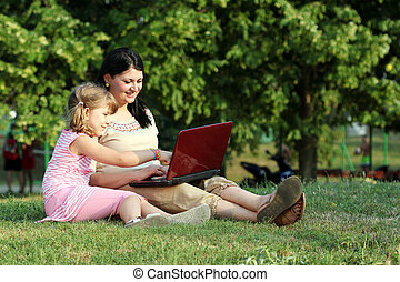 child and girl with laptop in park