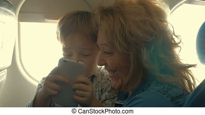 Child and grandmother entertaining with phone in plane