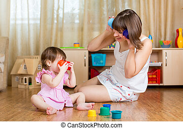 child and her mother playing together with toys