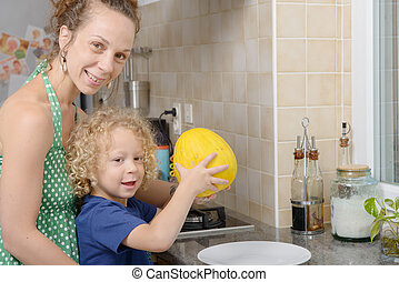 child and his mother with melon in kitchen