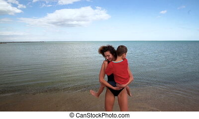 Child and mom on a beach are played, embrace and kiss. Slow motion. 120 fps