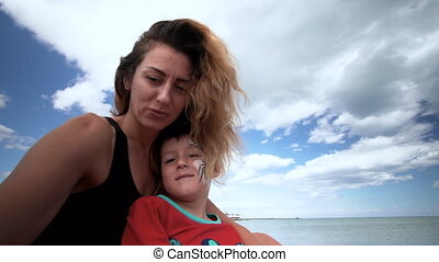Child and mom on a beach are played, embrace . Selfie