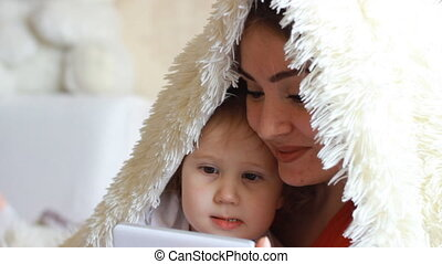 Child and mother Looks cartoons and plays downloaded application on a smart phone close-up. Mom and daughter lies in bed under the blanket and looks at the white phone screen