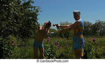 Child and mother play with water in summer day