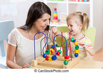 child and mother playing together with educational toy in...