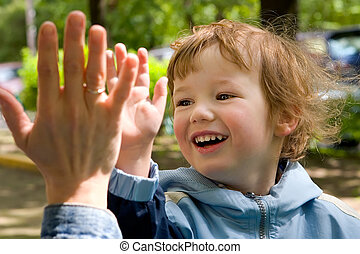 Child cheerfully plays with gentle and kind hands of mum