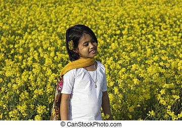 a beautiful indian girl child in white dress standing near yellow mustard flower field