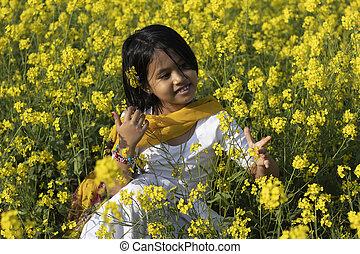 a beautiful indian innocent girl child in white dress sitting near yellow mustard flower field