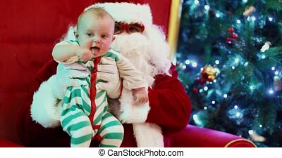 Child and Santa Claus sitting near glowing fir tree