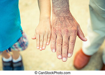 Child and senior man comparing his hands size over a nature path background. Two different generations concept.