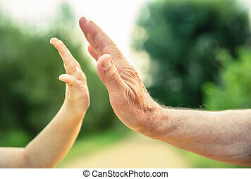 Child and senior man hands giving five in the nature
