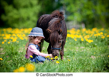 Small girl with horse in the meadow at spring.